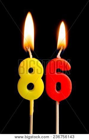 Burning Candles In The Form Of 86 Eighty Six (numbers, Dates) For Cake Isolated On Black Background.