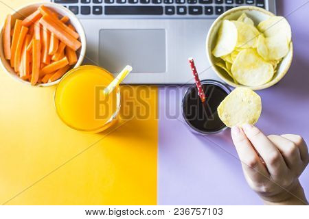 A woman chooses a harmful snack by chips and cola instead of juice and carrots. Eating in a break be