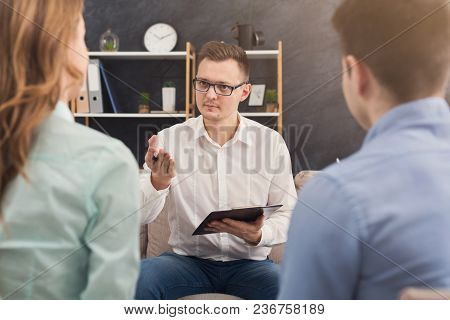 Young Couple Sitting On Couch During Therapy Session, Back View. Therapist Listening And Giving Advi