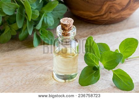 A Transparent Bottle Of Essential Oil With Fresh Marjoram Twigs On A Table