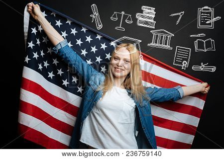 Patriotic Woman. Cheerful Young Happy Woman Looking Patriotic While Holding A Big Flag Of The Usa Af