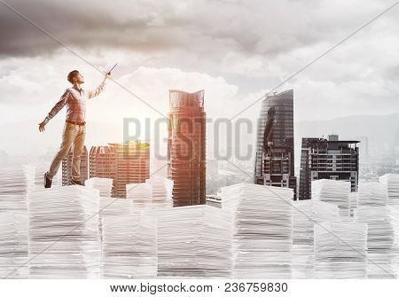 Side View Of Man In Casual Wear Keeping Hand With Book Up While Standing On Pile Of Documents With C