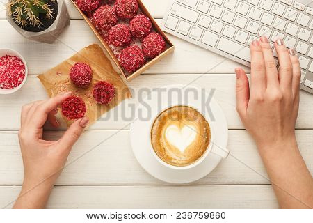 Female Hands Holding Coffee Cup At Working Table With Healthy Raw Vegan Candies, Nuts Assortment And