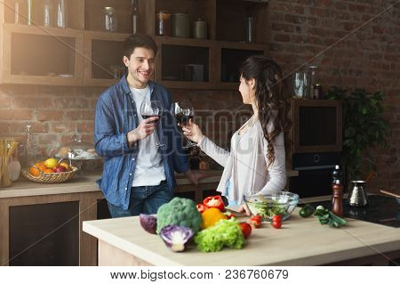 Happy Couple Cooking Healthy Food And Drinking Wine Together In Their Loft Kitchen At Home. Preparin