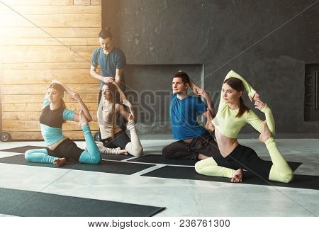 Yoga Teacher And Beginners In Class, Making Asana Exercises. Mermaid Pose. Healthy Lifestyle In Fitn