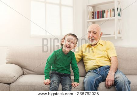 Happy Little Boy Sitting On Couch With His Grandfather, Having Fun Together. Family Time, Love And P