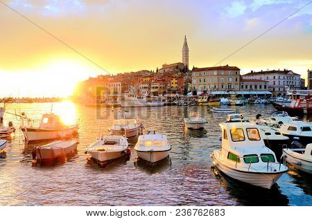 Old Town And Harbor With Boats And Vibrant Sunset Over The Sea, Rovinj, Croatia