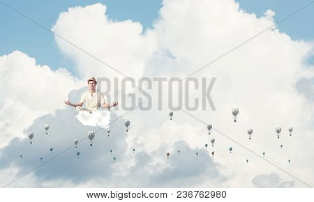 Man In White Clothing Keeping Eyes Closed And Looking Concentrated While Meditating Among Flying Aer