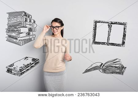 Cheerful Teacher. Clever Cheerful Teacher Touching Her Glasses While Waiting For Her Pupils In The C