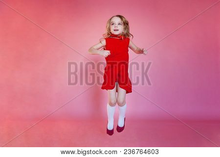 Little Cute Sweet Smiling Girl In Red Dress Jumping On Pink Colourful Pastel Trendy Modern Fashion P