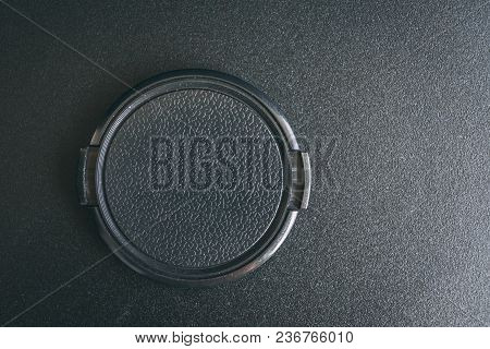 Black Camera Lens Cap On The Black Textured Table. Flat Lay With Copy Space For Text