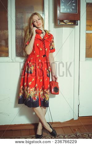 Beautiful Blond Woman With An Old Wired Phone Dressed In A Red Dress, Standing In An Old House, Vint