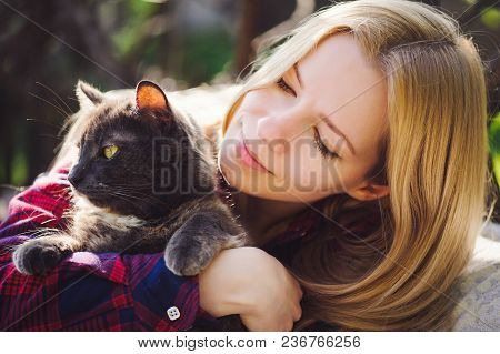 Beautiful Blonde Woman With A Cat In Nature, Bright And Sunny. Pets
