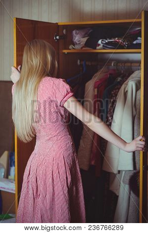 Blonde Woman Looks In A Closet, Dressed In A Red Dress, Stands In An Old House, A Simple Home Image