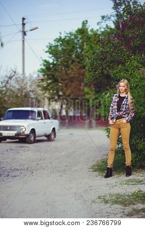 Pretty Blonde Woman On A Rustic Road, Against A Background Of Lots Of Green Trees And A Car, A Beaut