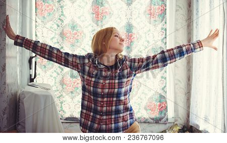 Pretty Blond Woman With Long Hair, A Beautiful Portrait In The House Rejoices Hands On The Sides, A