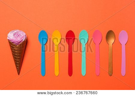 A Horn With Ice Cream Or With A Cream And Many Multicolored Spoons Are Lined Up In A Row, A Concept,