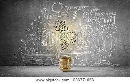 Lightbulb With Multiple Sketched Gears Inside Placed Against Eco-analytical Information Drawn On Gre