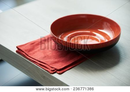 Red Empty Plate Or Soup Bowl And Red Napkin Serving On A Wooden Kitchen Table, Close-up