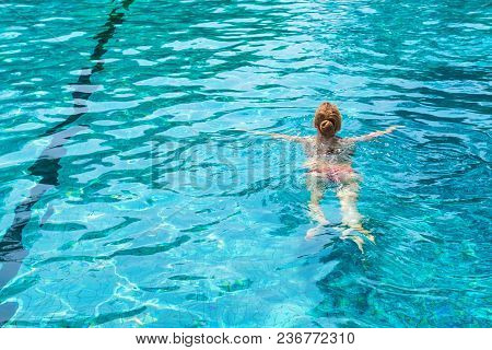 Back View Of Slim Young Beautiful Woman In Colorful Swimsuit Swimming In Swimming Pool. Enjoying Tro