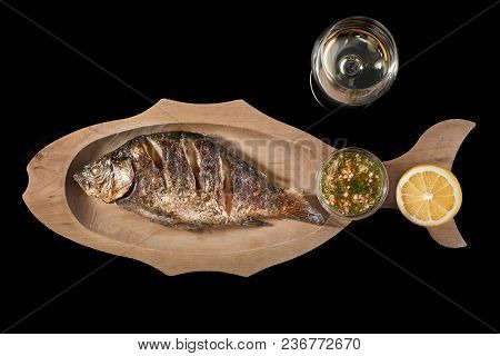 Fried Dorado Fish With Lemon And A Glass Of White Wine On A Black Background. Copy Space. Close Up,