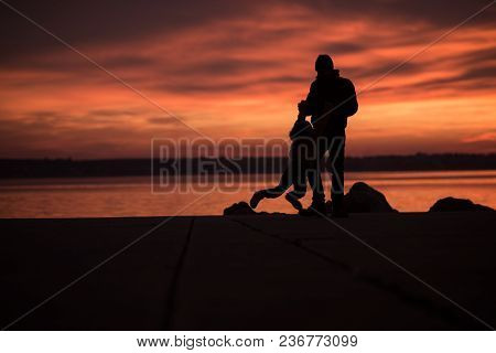 Young Boy Playing On Rocks With His Father Silhouetted Against A Glowing Orange Marine Sunset Reflec