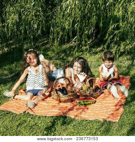 Cute Happy Family On Picnic Laying On Green Grass Mother And Kids, Warm Summer Vacations Close Up, B