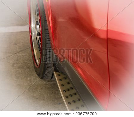 Closeup Of Red Sport Utility Vehicle Running Panel And Front Left Tire With Red Rims.