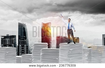 Businessman Keeping Hand With Book Up While Standing On Pile Of Paper Documents With Cityscape And S