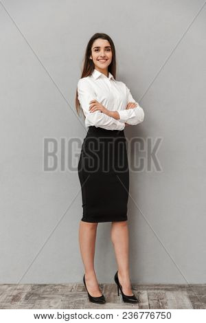 Full length portrait of caucasian woman with long brown hair in business wear smiling at camera and keeping arms crossed isolated over white background