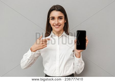 Caucasian woman with long brown hair doing commercial and presenting black copyspace screen of mobile phone at camera isolated over gray background