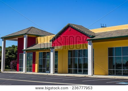 Vacant Corner Commercial Store Front Building With Blue Sky Background