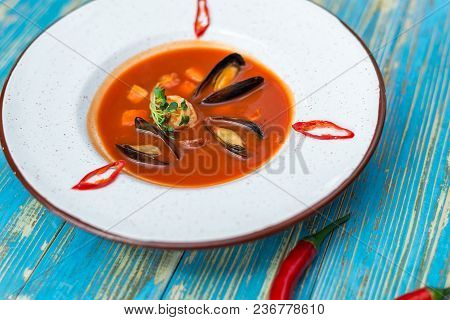 Red Soup With Oysters In A White Plate