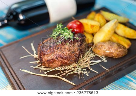 Steak With Potatoes On A Wooden Board