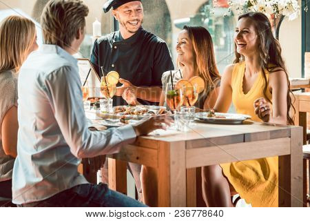 Experienced chef smiling congratulated for the delicious food by four young people at the table of a trendy exclusive restaurant