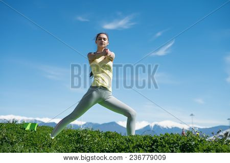 Confident Young Girl Doing Yoga On Green Grass On A Warm Spring Day, Stretching
