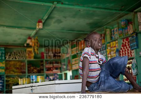 BOR, SOUTH SUDAN-DECEMBER 3, 2010: An unidentified child showing signs of diphtheria watches his parents small shop in the town of Bor, South Sudan.