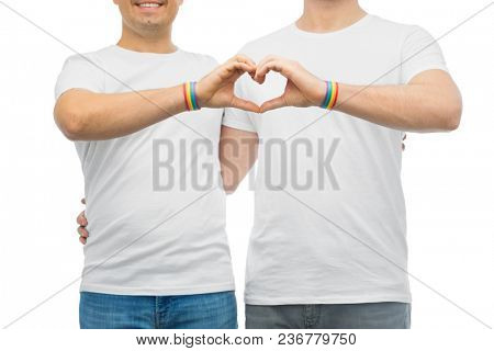 lgbt, same-sex love and homosexual relationships concept - close up of happy smiling hugging male couple wearing gay pride rainbow awareness wristbands showing hand heart gesture
