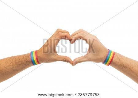 lgbt, same-sex love and homosexual relationships concept - close up of male couple hands with gay pride rainbow awareness wristbands showing heart gesture