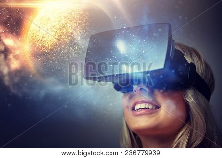 technology, augmented reality and people concept - happy young woman with virtual headset or 3d glasses over planet and space background