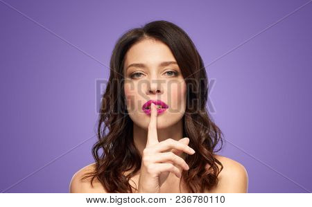 beauty, secret, make up and people concept - beautiful woman holding finger on lips or mouth with pink lipstick over ultra violet background