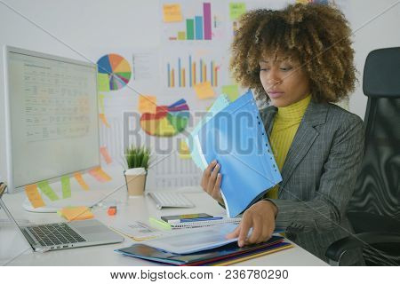 Concentrated young entrepreneur sitting at table in stylish office and exploring files with paper documents looking serious.