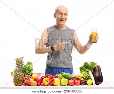 Senior behind a table with fruit and vegetables holding a glass of juice and pointing isolated on white background
