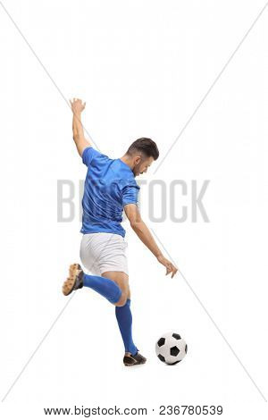 Full length rear view shot of a soccer player kicking a football isolated on white background