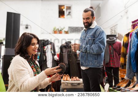 sale, shopping, footwear and people concept - happy couple choosing loafer shoes at vintage clothing store