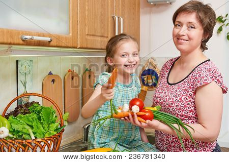 Mother and daughter cooking. Basket of vegetables and fresh fruits in kitchen interior. Parent and child. Healthy food concept