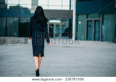 Business woman with eyeglasses and laptop in hands, back view. Modern building, financial center, cityscape. Successful female businessperson