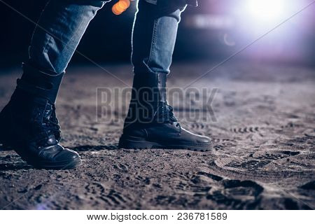Scary view of male legs, car light at the night on background