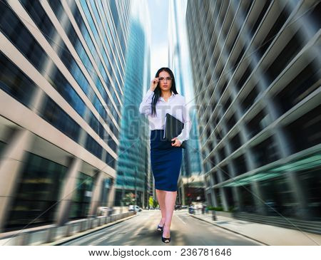 Portrait of young business woman in glasses and white blouse with notebook in hand, bottom view, blur skyscapers on background. Modern building, financial center. Successful female businessperson