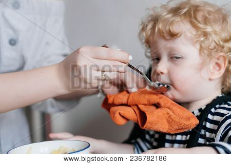 A Caring Young Mother Feeds Her Little Curly Son With Useful Porridge, A Family Breakfast